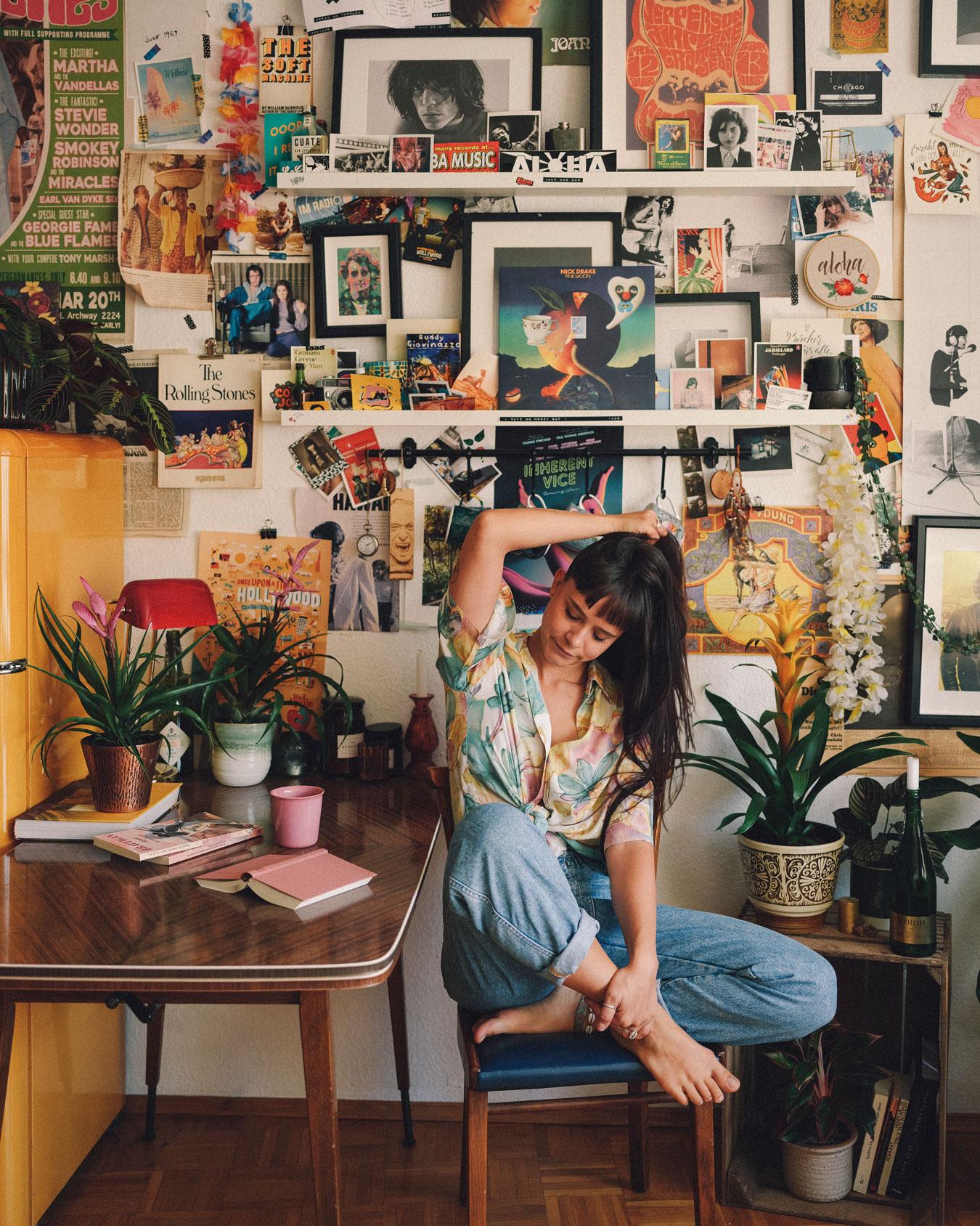 Frau sitzt vor Wand mit Bildern und Bromelien Junestorm