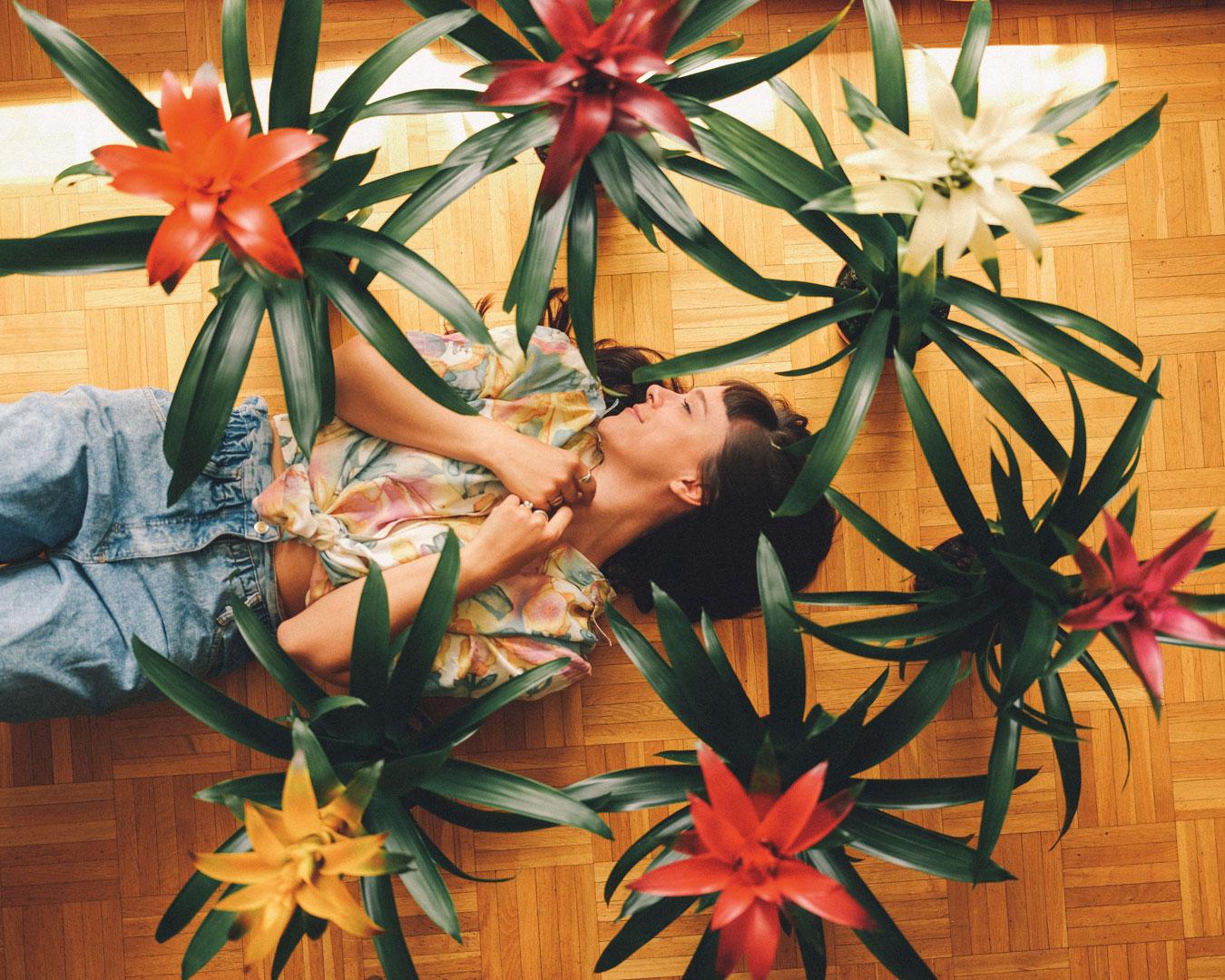 Frau liegt auf Boden mit Blumen Pflanzen Bromelien