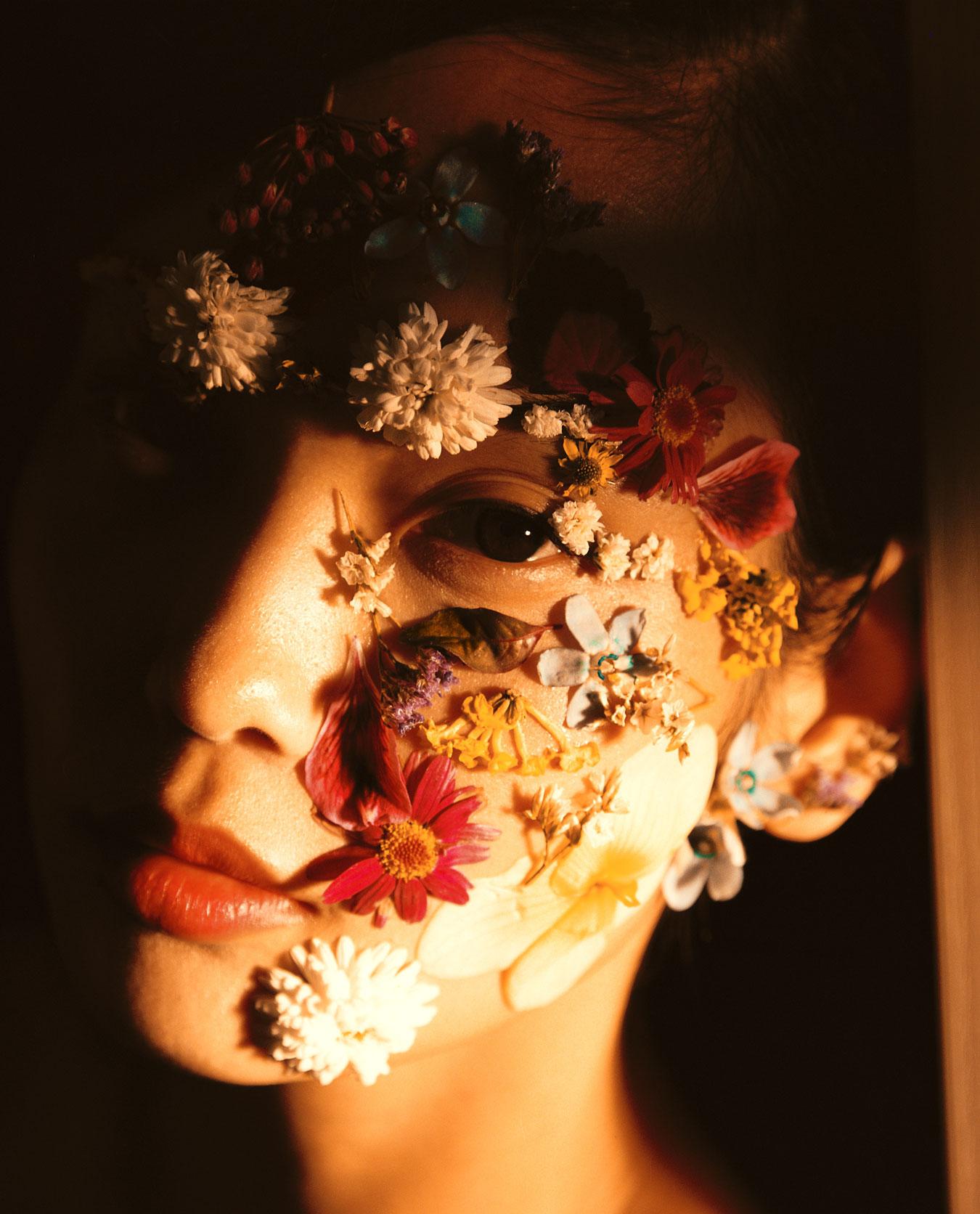 Clean Beauty Frau mit Blumenblüten im Gesicht